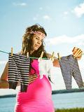 Beautiful pregnant woman and children clothes Stock Photo