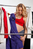 Beautiful pregnant woman choosing what to wear Stock Photography