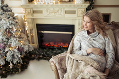 Beautiful Pregnant Woman In Comfy Clothes. Sitting In A Chair Near The Christmas Tree Royalty Free Stock Images