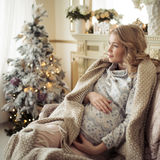 Beautiful Pregnant Woman In Comfy Clothes. Sitting In A Chair Near The Christmas Tree Royalty Free Stock Photo