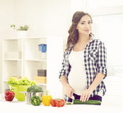Beautiful pregnant woman cooking in the kitchen Stock Photography