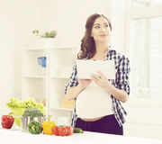 Beautiful pregnant woman cooking in the kitchen Stock Photos
