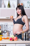 Beautiful pregnant woman cooks Royalty Free Stock Images