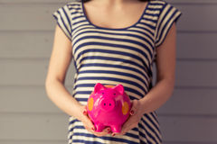 Beautiful pregnant woman. Cropped image of beautiful pregnant woman holding a piggy bank while standing against gray wall Royalty Free Stock Photo