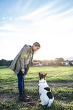 Beautiful pregnant woman with dog in green sunny nature. Beautiful young pregnant woman on a walk with a dog, feeding him. Green sunny nature Royalty Free Stock Photo
