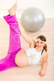 Beautiful pregnant woman doing fitness exercises. Smiling beautiful pregnant woman doing fitness exercises at living room Stock Photography