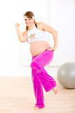 Beautiful pregnant woman doing fitness exercises. Smiling beautiful pregnant woman doing fitness exercises at living room Stock Images