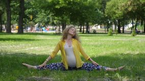 Beautiful pregnant woman doing prenatal yoga on nature outdoors. Sport, fitness, healthy lifestyle while pregnancy. Pregnant woman practicing yoga pose stock video footage