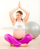 Beautiful pregnant woman doing yoga on floor Royalty Free Stock Photo