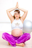 Beautiful pregnant woman doing yoga on floor Stock Photos