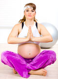Beautiful pregnant woman doing yoga on floor Stock Images