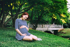 Beautiful pregnant woman in dress on nature. Beautiful pregnant woman in dress on nature, outdoors with copy space. Expectant mother holds hands on belly on Royalty Free Stock Photography