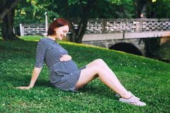 Beautiful pregnant woman in dress on nature. Beautiful pregnant woman in dress on nature, outdoors with copy space. Expectant mother holds hands on belly on Stock Photo