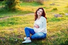 Beautiful pregnant woman in dress on nature, outdoors with copy space. Expectant mother holds hands on belly on natural Stock Photography