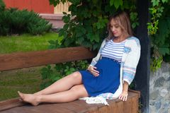 A beautiful pregnant woman in a dress sitting on a branch and touching her belly with love and care. Walking in the park Royalty Free Stock Photo