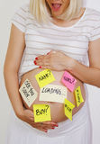 Beautiful pregnant woman expecting concept. Expecting concept tags on sticker notes about pregnancy and babies royalty free stock photo