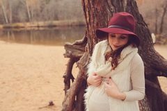 Beautiful pregnant woman in fashion hat on cozy warm outdoor walk Stock Photo