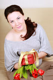Beautiful pregnant woman with gift and tulips Royalty Free Stock Images