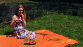 Beautiful pregnant woman girl eat grapes sit on plaid near river Stock Images