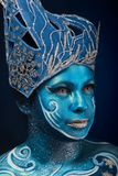 Beautiful pregnant woman with headwear and abstract body art. In shades of blue and white