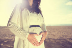 Beautiful pregnant woman with heart shape hands gesture on the b Royalty Free Stock Photos