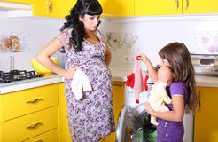 Beautiful pregnant woman with her little  daughter beside a washing machine Royalty Free Stock Image
