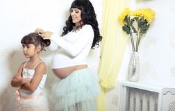 Beautiful pregnant woman with her little funny daughter Stock Photos