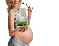 Beautiful pregnant woman hold organic salad and fork with tomato. Pregnancy motherhood expectation healthy eating Stock Images
