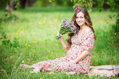 Beautiful pregnant woman holding flowers outdoors Royalty Free Stock Photos