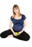 Beautiful pregnant woman holding green apple. Looking to the camera isolated on white Royalty Free Stock Photo