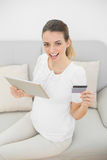 Beautiful pregnant woman holding her credit card and tablet looking cheerfully at camera Stock Photo