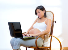 Beautiful pregnant woman at home with laptop Royalty Free Stock Image