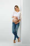 Beautiful pregnant woman in jeans Stock Images