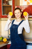 Beautiful pregnant woman at kitchen with orange Stock Images