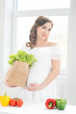 Beautiful pregnant woman in the kitchen Royalty Free Stock Image