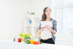 Beautiful pregnant woman in the kitchen surfing in tablet Royalty Free Stock Photography