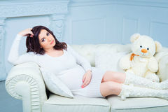 Beautiful pregnant woman in knitted clothes on white sofa with teddy bear Stock Photo
