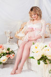 Beautiful pregnant woman in a lace negligee sitting on a bed of flowers Royalty Free Stock Photos