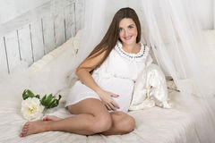 Beautiful pregnant woman laying in bed Stock Photos