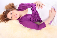 Beautiful pregnant woman lies on white fur royalty free stock photos