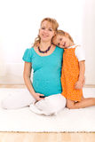 Beautiful pregnant woman and little girl hugging Royalty Free Stock Photos