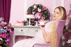 Beautiful pregnant woman. With long hair drinking tea royalty free stock photography