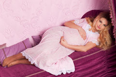 Beautiful pregnant woman. With long hair lying on the sofa royalty free stock image