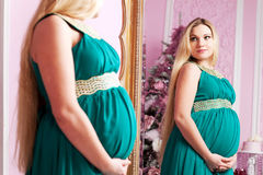 Beautiful pregnant woman. With long hair near a mirror stock images