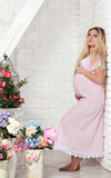 Beautiful pregnant woman. With long hair near white wall stock photos
