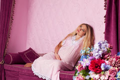 Beautiful pregnant woman. With long hair sitting on the sofa stock photo