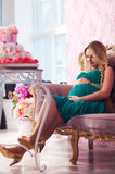 Beautiful pregnant woman. With long hair sitting on the sofa stock photography