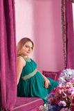 Beautiful pregnant woman. With long hair sitting on the sofa stock images