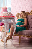Beautiful pregnant woman. With long hair sitting on the sofa stock photos