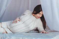 Beautiful Pregnant Woman lying in bed with canopy. Wears white knitted pullover. Maternity concept royalty free stock photography
